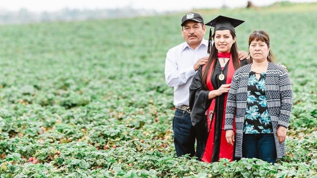 Une diplômée pose avec ses parents dans le champ de fruits où ils travaillent