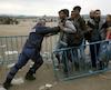 A Greek policeman pushes refugees behind a barrier near the Greek-Macedonian border