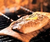 seasoned salmon fillet cooking on cedar plank over grill