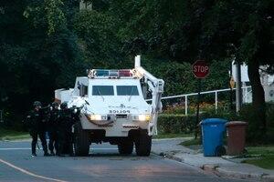 Vers 5 h 30, un véhicule blindé de la Sûreté du Québec a enfoncé la porte avant, ainsi que des fenêtres de la résidence où 200 armes ont été saisies (à droite).