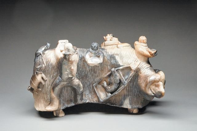 <b><i>Shaman's Muskox (bœuf musqué du shaman)</i></b><br /> <b>Sans date. Grès cuit en atmosphère réductrice, 53x30,5x23cm</b><br /> Les œuvres complexes d'Aksadjuak adoptent des formes multiples et une imagerie ludique, tout en respectant les récits traditionnels. Collection particulière. Œuvre de  Roger Aksadjuak.