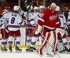 Le gardien des Red Wings Jared Coreau quitte la glace alors que les joueurs des Rangers célèbrent leur victoire en prolongation.