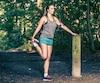 Junge Frau macht Dehnübungen im Wald