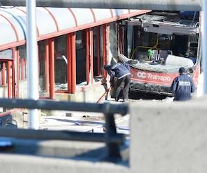 Des policiers inspectant la scène de l'accident mortel impliquant un autobus à deux étages d'OC Transpo et un abribus, survenu vendredi en fin d'après-midi à Ottawa.