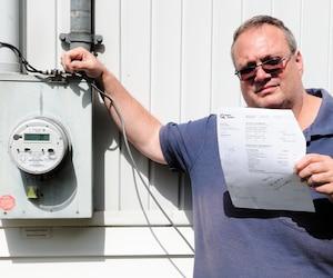 Marc Dallaire, de Sainte-Marthe-sur-le-Lac, tient safacture d'Hydro-Québec pour le mois où il n'a pas consommé d'électricité pendant trois semaines, et devant le compteur intelligent qui n'est pas le sien selon le numéro de série.