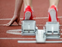 Detailed view of a sprinter wearing sprinting shoes with spikes, leaving starting blocks