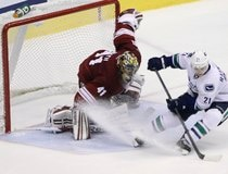 Vancouver Canucks' Raymond tries to spin away from the Phoenix Coyotes goalie Smith during their shootout in their NHL hockey game in Glendale