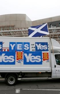 A van covered in 'Yes' campaign posters drives past the Scottish Parliament building in Edinburgh