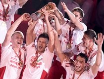 Poland's Zagumny, Winiarski and Drzyzga lift the trophy as their team celebrate on the podium after defeating Brazil to win the Volleyball Men's World Championship final at Spodek Arena in Katowice