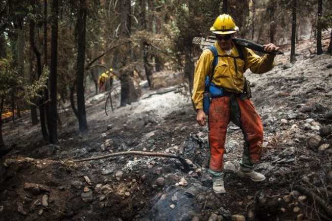 Firefighters mop up a spot fire on the northern edge of the King Fire in the Tahoe National Forest