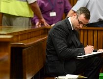 Olympic and Paralympic track star Oscar Pistorius takes notes during his sentencing hearing at the North Gauteng High Court in Pretoria