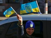 A man waves national Ukraine flags from a car in the town of Slavyansk