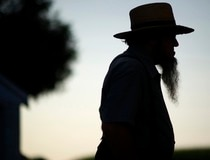 A silhouetted Amish man waits during his buggy tour in Lancaster County, Pennsylvaniaty