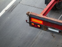 Back part with taillight of empty truck cargo trailer on the asphalt road