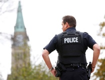 A police officer stands guard with the Peace Tower in the background following shootings in downtown Ottawa