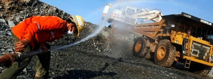 A miner sprays water to reduce the dust as a truck is loaded at hatree gold mine operated by Akara Mining in Phichin