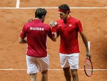 Switzerland's Federer reacts with his team mate Wawrinka during their Davis Cup final doubles tennis match against France's Benneteau and Gasquet at the Pierre-Mauroy stadium in Villeneuve d'Ascq, nea