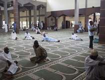 Men sit after a Ramadan Tafsir session at the Grand Mosque in Kaduna