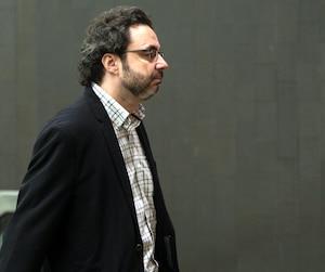 L'auteur Maxime Roussy s'est présenté au palais de justice de Montréal avec sa valise mardi. Il est reparti en fourgon cellulaire.