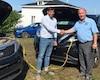 Le candidat du Bloc québécois Guy Bernatchez et celui du Parti conservateur Jean-Pierre Pigeon, alors que le premier a reçu l'aide du second pour survolter la batterie de son véhicule.
