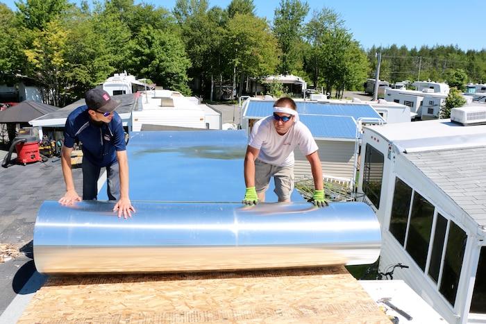 Une fois que la toiture a été soigneusement préparée, les ouvriers déroulent l'immense feuille de tôle d'aluminium qui viendra sceller le toit pour longtemps.