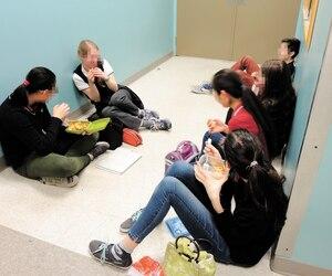 Des élèves mangent dans un des couloirs de l'école Sophie-Barat. «Quand il fait beau, c'est moins pire parce qu'ils sortent dehors, mais l'hiver, et dès qu'il pleut, c'est épouvantable», dit Suzanne Leduc, gestionnaire.