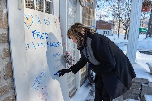 La mairesse du Lac-Beauport Louise Brunet écrit un mot sur le tableau placé devant la maison de la famille.