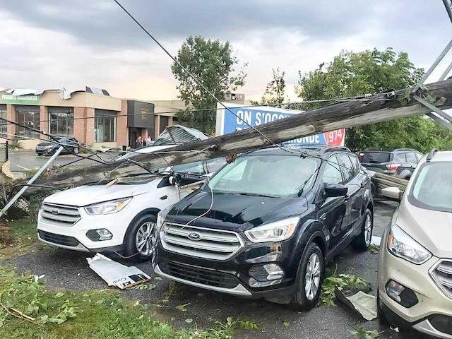 Un concessionnaire automobile a vu certains de ses VUS être aplatis par un poteau renversé par le vent.