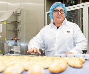 Une employée de Bridor à l'usine de Boucherville s'apprête à mettre les pâtisseries au four en vue de la grande production de la journée.