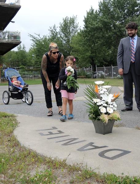 La petite Zhaïa Côté-Morin, 4 ans et demi, dépose des fleurs sur le mémorial de Daniel Desrochers dans la cour de l'école Saint-Nom-de-Jésus, dans Hochelaga-Maisonneuve.