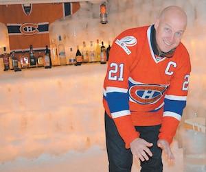 Derek Parker se réchauffe dans son igloo grâce à un foyer au gaz propane. En arrière-plan, un bar et une lumière de but ajoutent à l'ambiance.
