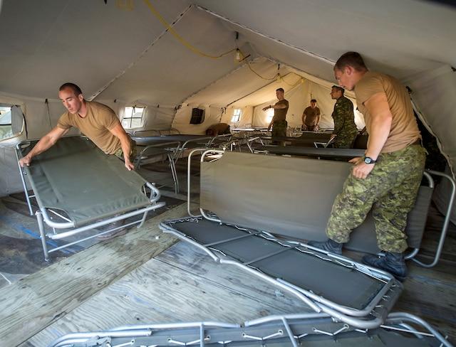 Les militaires plaçaient mercredi soir le plancher, puis les lits où dormiront les migrants en attente aux douanes.