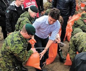 Justin Trudeau a rempli quelques sacs de sable le temps de faire des belles images en compagnie de sa femme (derrière lui sur la photo), jeudi. Il a récidivé en compagnie de ses fils, samedi.