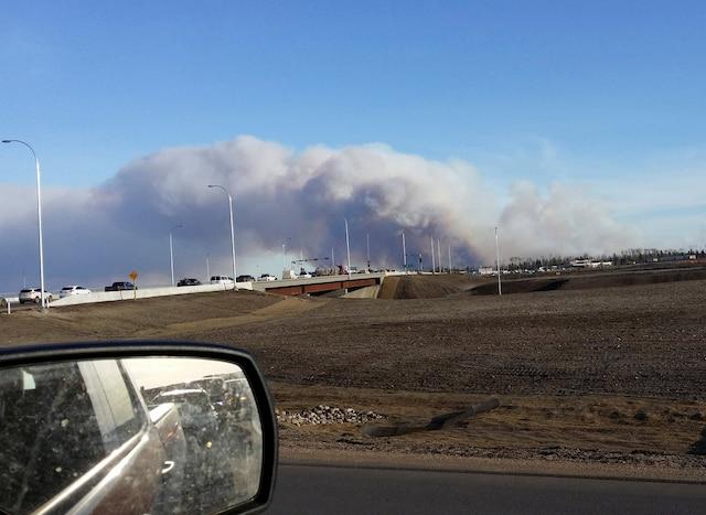 Des véhicules circulent sur l'autoroute 63 alors que le feu fait rage près de Fort McMurray.
