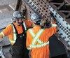 Deux travailleurs s'affairant à la réparation temporaire de la structure sur l'approche nord-est du pont.