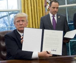 Donald Trump montrant le décret présidentiel à la caméra.
