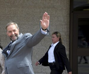 New Democratic Party leader Thomas Mulcair waves as he is cheered on by the public following a news conference in Gatineau