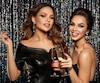 Two beautiful young girls smiling and holding a glass of champagne, meeting Christmas and New Year. Clean skin and a hairstyle with bright lips. Photographed on a sparkling background.