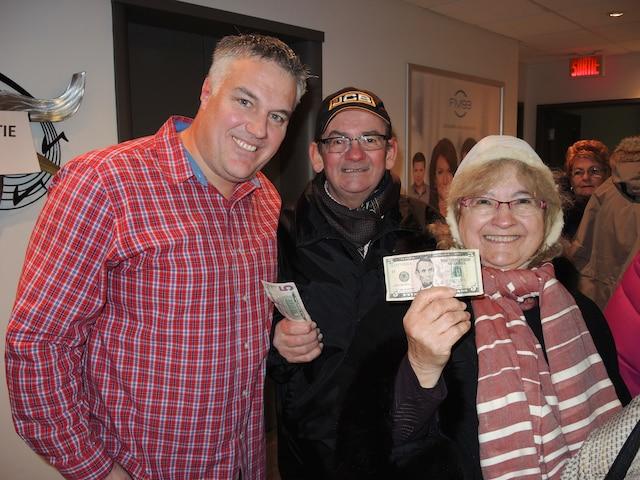 L'animateur sportif Dan Pou reçoit les gens à la station qui viennent s'inscrire pour le tirage record de la loterie américaine Powerball.