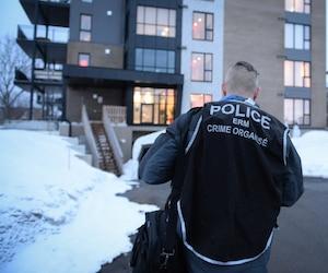 Un enquêteur photographié en face de l'immeuble à condos où habite le Hells Angel Mario Brouillette, mercredi, à Repentigny.
