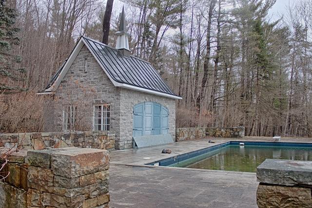 La piscine extérieure à flanc de boisé.