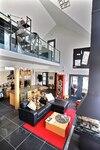 La pièce à aire ouverte est propice aux moments de détente, de contemplation et aux réceptions en famille ou entre amis. L'escalier au garde-corps de verre mène à l'étage consacré au travail.
