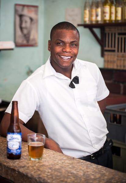 Notre jasant barman accoudé fièrement à son bar.
