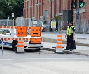 Un policier en uniforme du Service de police de la Ville de Montréal gérait la circulation lundi à l'angle des rues Wellington et Queen.