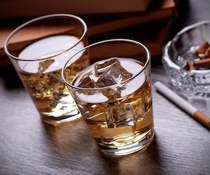bicchieri di whisky, libri e sigarette