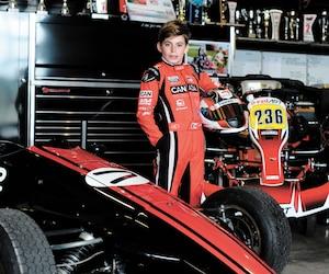 Le jeune champion canadien de karting Justin Arseneau, 12 ans, pose aux côtés de son bolide dans les garages du circuit ICAR à Mirabel. Il a été sélectionné pour accompagner les pilotes de F1 pour le départ final du Grand Prix du Canada aujourd'hui.