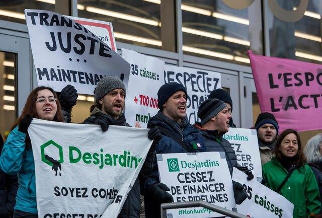 Une soixantaine de personnes se sont rassemblées devant le palais des congrès pour dénoncer tout financement et investissements dans les pipelines de sables bitumineux par Desjardins, lors de l'assemblée générale annuelle de la Fédération des caisses Desjardins, à Montréal, samedi le 30 mars 2019.
