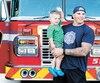 Le pompier et athlète Jean-Sébastien Martel tient dans ses bras son fils James, qui est atteint de l'hémiparésie.
