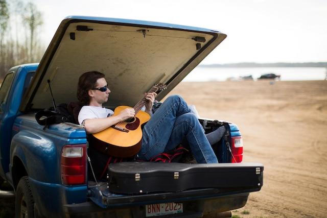 Le professeur de guitare Justin Ferrari relaxe à l'arrière de sa camionnette stationnée sur une plage au sud de Fort McMurray après avoir été évacué, mercredi.