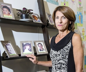La directrice du Réseau Enfants-Retour, Pina Arcamone, pose devant les photos de jeunes toujours portés disparus. «Ces photos sont affichées dans nos bureaux afin que ces enfants ne soient jamais oubliés», indique-t-elle.